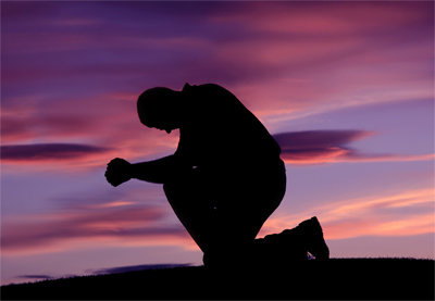 kneeling in prayer sunset